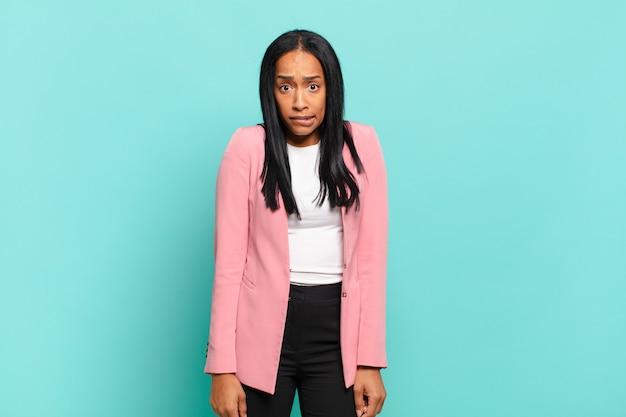 Jonge zwarte vrouw die verbaasd en verward kijkt, lip bijt met een nerveus gebaar, niet wetend het antwoord op het probleem. bedrijfsconcept