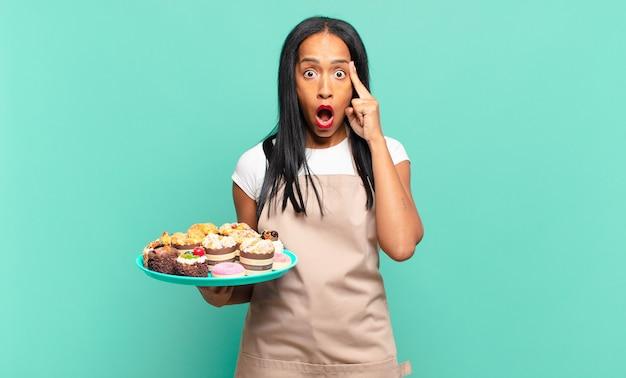 Jonge zwarte vrouw die verbaasd, met open mond, geschokt kijkt, een nieuwe gedachte, idee of concept realiseert. bakkerij chef-kok concept