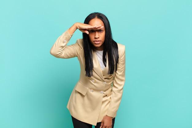 Jonge zwarte vrouw die verbijsterd en verbaasd kijkt, met hand over voorhoofd ver weg kijkend, kijkend of zoekend