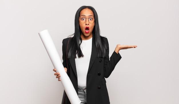 Jonge zwarte vrouw die verrast en geschokt kijkt, met open mond terwijl ze een object vasthoudt met een open hand aan de zijkant. architect concept