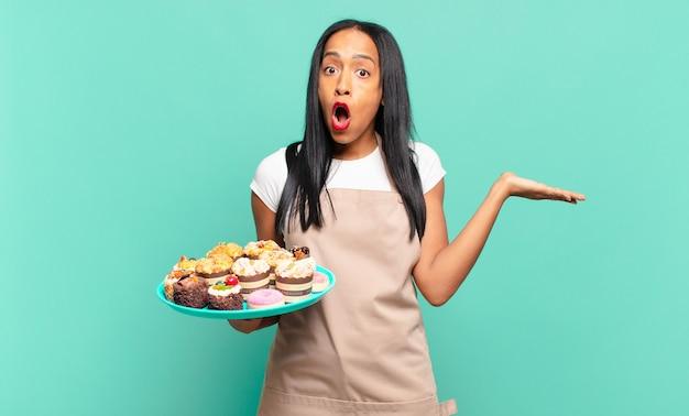 Jonge zwarte vrouw die verrast en geschokt kijkt, met open mond terwijl ze een object vasthoudt met een open hand aan de zijkant. bakkerij chef-kok concept