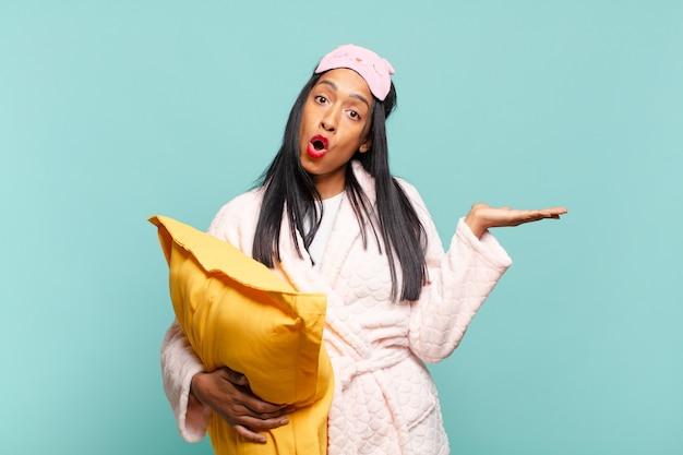 Jonge zwarte vrouw die verrast en geschokt kijkt, met open mond terwijl ze een object vasthoudt met een open hand aan de zijkant. pyjama concept