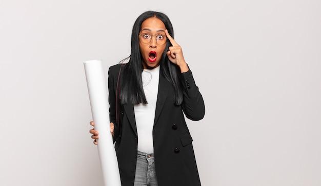 Jonge zwarte vrouw die verrast, met open mond, geschokt kijkt en een nieuwe gedachte, idee of concept realiseert