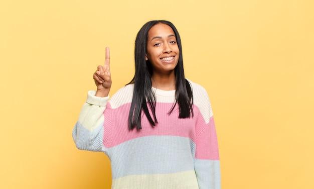 Jonge zwarte vrouw die vrolijk en gelukkig lacht en met één hand naar boven wijst om ruimte te kopiëren