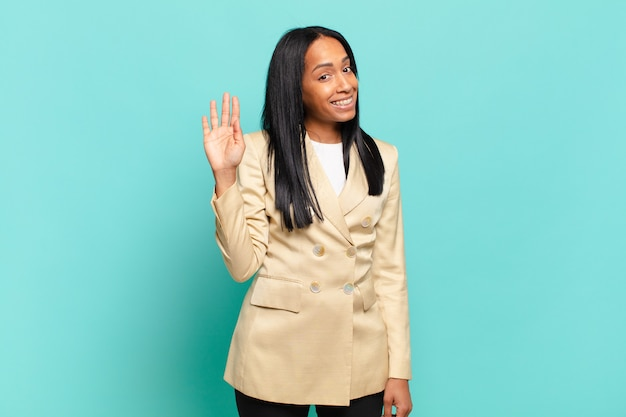 Jonge zwarte vrouw die vrolijk en opgewekt lacht, met de hand zwaait, je verwelkomt en begroet, of afscheid neemt