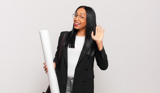 Jonge zwarte vrouw die vrolijk en vrolijk lacht, met de hand zwaait, je verwelkomt en begroet, of afscheid neemt. architect concept