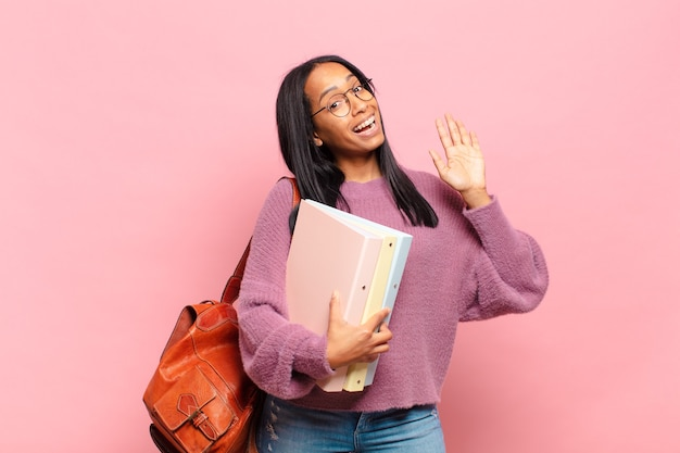 Jonge zwarte vrouw die vrolijk en vrolijk lacht, met de hand zwaait, je verwelkomt en begroet, of afscheid neemt. studentenconcept