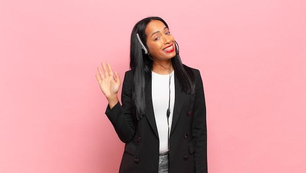 Jonge zwarte vrouw die vrolijk en vrolijk lacht, met de hand zwaait, je verwelkomt en begroet, of afscheid neemt. telemarketing concept