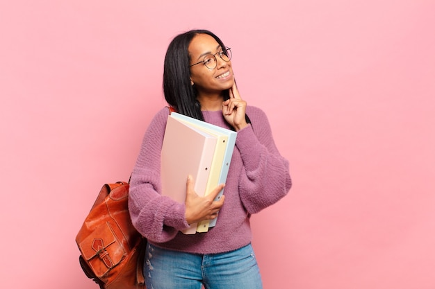 Jonge zwarte vrouw die vrolijk lacht en dagdroomt of twijfelt, opzij kijkend. studentenconcept