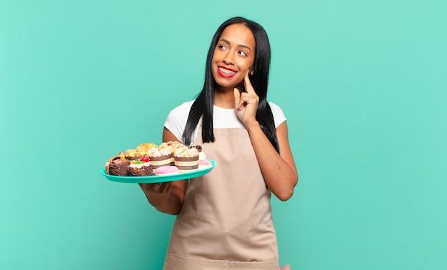 Jonge zwarte vrouw die vrolijk lacht en dagdroomt of twijfelt, opzij kijkend.