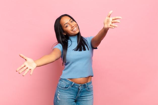 Jonge zwarte vrouw die vrolijk lacht en een warme, vriendelijke, liefdevolle welkomstknuffel geeft, zich gelukkig en schattig voelt