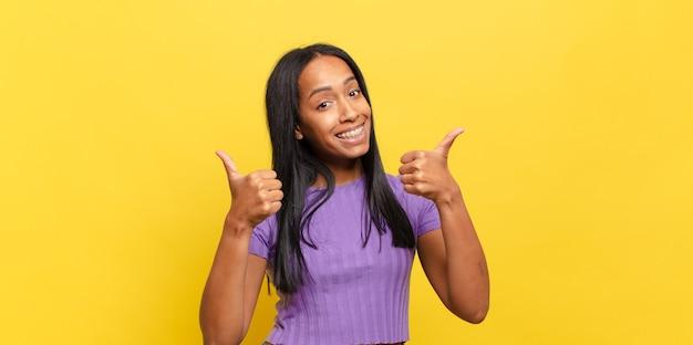 Jonge zwarte vrouw die vrolijk lacht en er gelukkig uitziet, zich zorgeloos en positief voelt met beide duimen omhoog