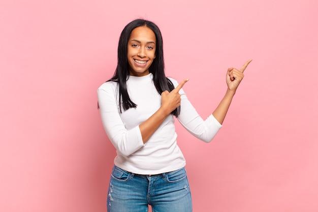 Jonge zwarte vrouw die vrolijk lacht en naar de zijkant en naar boven wijst met beide handen die een object in de kopieerruimte tonen