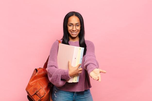 Jonge zwarte vrouw die vrolijk lacht met een vriendelijke, zelfverzekerde, positieve blik, een object of concept aanbiedt en toont. studentenconcept