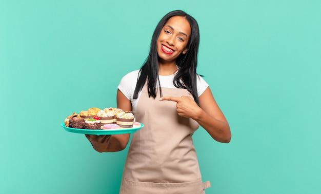 Jonge zwarte vrouw die vrolijk lacht, zich gelukkig voelt en naar de zijkant en naar boven wijst, een object in de kopieerruimte laat zien. bakkerij chef-kok concept