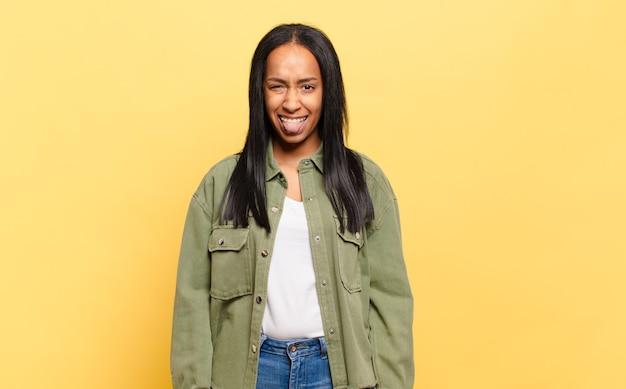 Jonge zwarte vrouw die walgt en geïrriteerd is, tong uitsteekt, een hekel heeft aan iets smerigs en vies