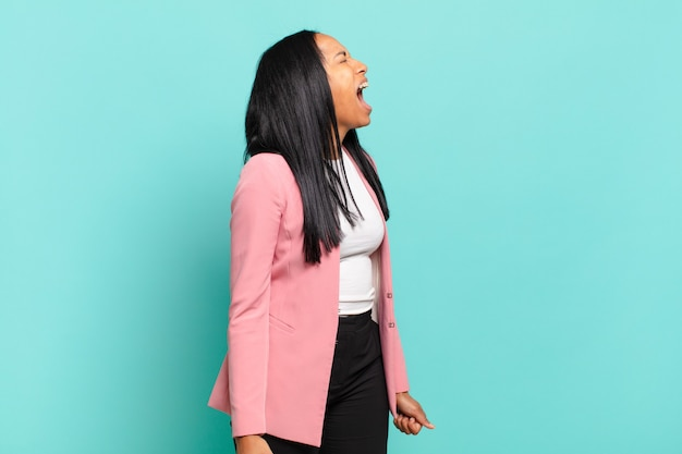 Jonge zwarte vrouw die woedend schreeuwt, agressief schreeuwt, er gestrest en boos uitziet. bedrijfsconcept