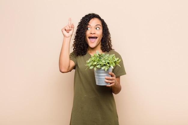 Jonge zwarte vrouw die zich als een gelukkig en opgewonden genie voelt na het realiseren van een idee, opgewekt de vinger opstekend, eureka! met een plant