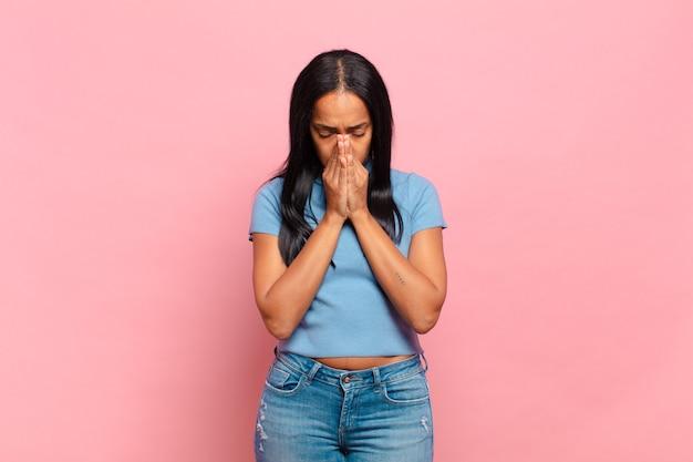 Jonge zwarte vrouw die zich bezorgd, hoopvol en religieus voelt, trouw bidt met ingedrukte handpalmen, smekend om vergiffenis