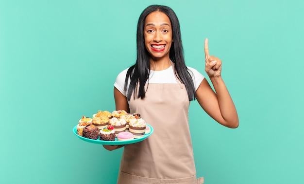 Jonge zwarte vrouw die zich een gelukkig en opgewonden genie voelt na het realiseren van een idee, vrolijk vinger opstekend, eureka!. bakkerij chef-kok concept