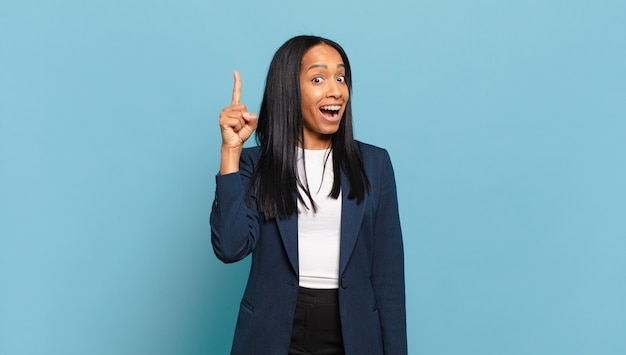 Jonge zwarte vrouw die zich een gelukkig en opgewonden genie voelt na het realiseren van een idee, vrolijk vinger opstekend, eureka!. bedrijfsconcept