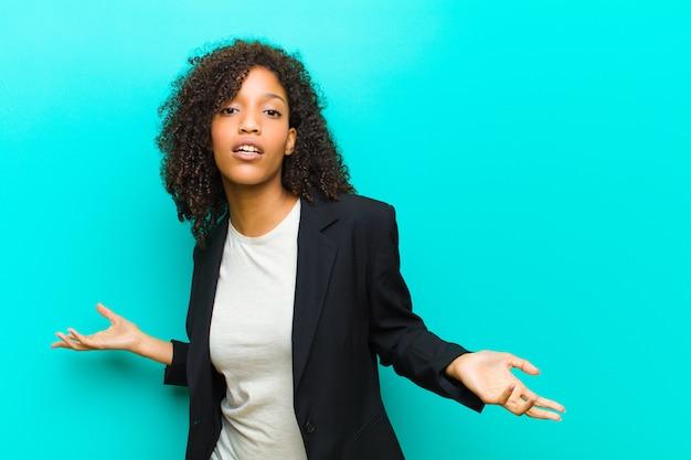 Jonge zwarte vrouw die zich geen idee heeft en verward is, geen idee heeft, absoluut verbaasd over een stompe of dwaze look blauwe muur