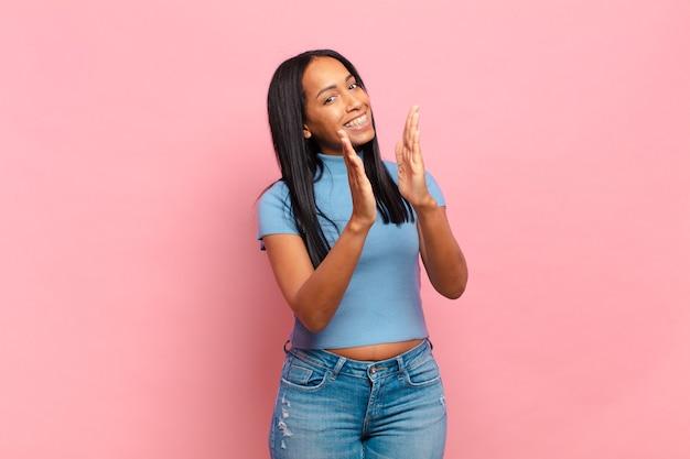 Jonge zwarte vrouw die zich gelukkig en succesvol voelt, lacht en in de handen klapt, gefeliciteerd met een applaus