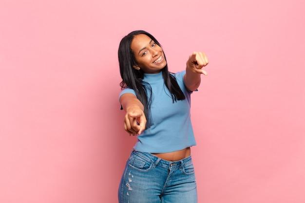 Jonge zwarte vrouw die zich gelukkig en zelfverzekerd voelt, met beide handen naar de camera wijst en lacht, jou kiest