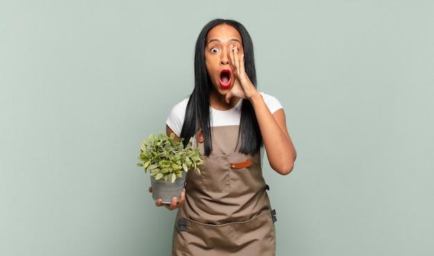 Jonge zwarte vrouw die zich gelukkig, opgewonden en positief voelt, een grote schreeuw geeft met de handen naast de mond, roept. tuinman concept