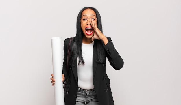 Jonge zwarte vrouw die zich gelukkig, opgewonden en positief voelt en een grote schreeuw geeft met de handen naast de mond