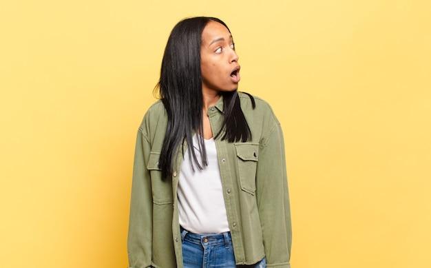 Jonge zwarte vrouw die zich geschokt, blij, verbaasd en verrast voelt