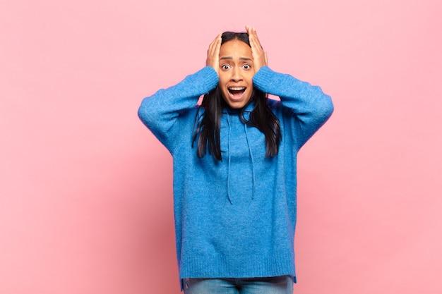 Jonge zwarte vrouw die zich geschokt en geschokt voelt, haar handen opheft en in paniek raakt bij een fout