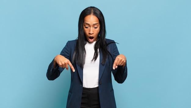Jonge zwarte vrouw die zich geschokt, met open mond en verbaasd voelt