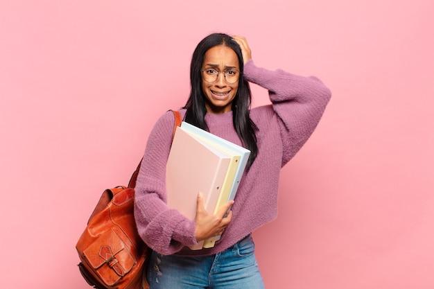 Jonge zwarte vrouw die zich gestrest, bezorgd, angstig of bang voelt, met de handen op het hoofd, in paniek bij vergissing. studentenconcept