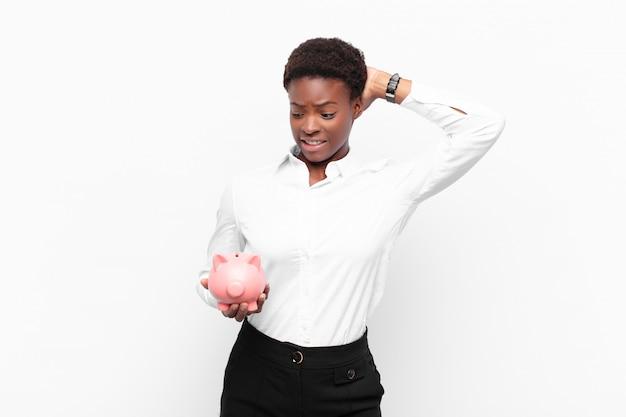 Jonge zwarte vrouw die zich gestrest, bezorgd, angstig of bang voelt, met de handen op het hoofd, in paniek raakt bij een fout met een spaarvarken