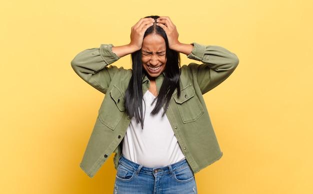 Jonge zwarte vrouw die zich gestrest en gefrustreerd voelt, de handen naar het hoofd heft, zich moe, ongelukkig en met migraine voelt