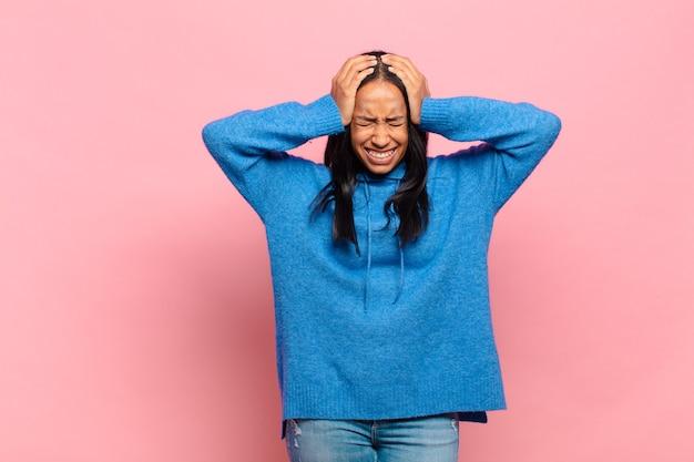 Jonge zwarte vrouw die zich gestrest en gefrustreerd voelt, handen tegen het hoofd steekt, zich moe, ongelukkig en met migraine voelt