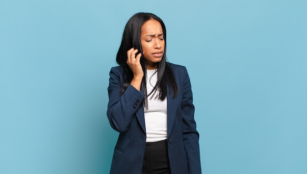 Jonge zwarte vrouw die zich gestrest, gefrustreerd en moe voelt, pijnlijke nek wrijft, met een bezorgde, onrustige blik. bedrijfsconcept