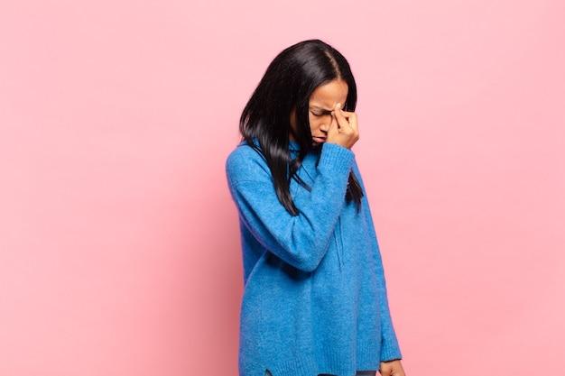 Jonge zwarte vrouw die zich gestrest, ongelukkig en gefrustreerd voelt, het voorhoofd aanraakt en lijdt aan migraine of ernstige hoofdpijn