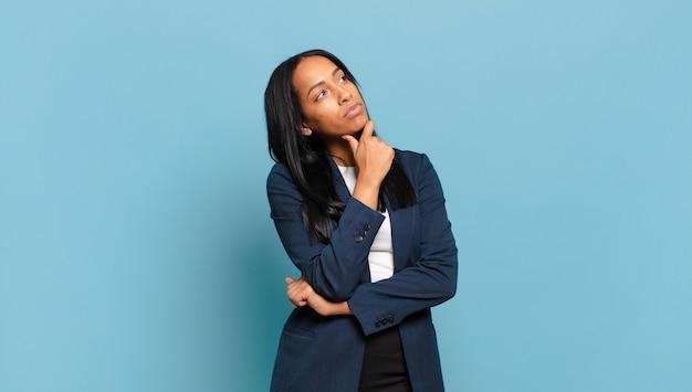 Jonge zwarte vrouw die zich nadenkend voelt, zich afvraagt of zich ideeën voorstelt
