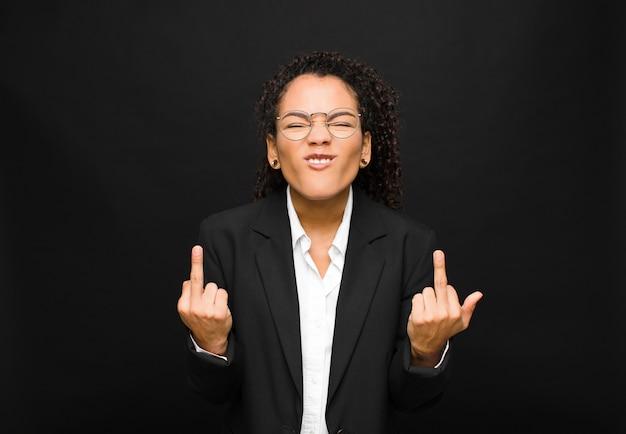 Jonge zwarte vrouw die zich provocerend, agressief en obsceen voelt, de middelvinger omdraait, met een rebelse houding tegen de zwarte muur