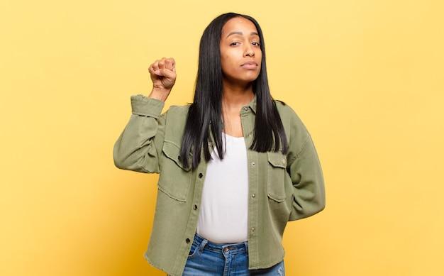 Jonge zwarte vrouw die zich serieus, sterk en rebels voelt, vuist opstekend, protesteert of vecht voor revolutie