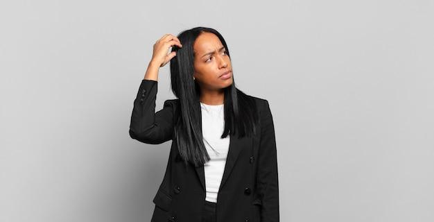 Jonge zwarte vrouw die zich verbaasd en verward voelt, haar hoofd krabt en opzij kijkt. bedrijfsconcept