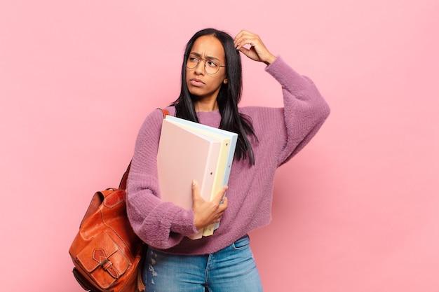 Jonge zwarte vrouw die zich verbaasd en verward voelt, haar hoofd krabt en opzij kijkt. studentenconcept