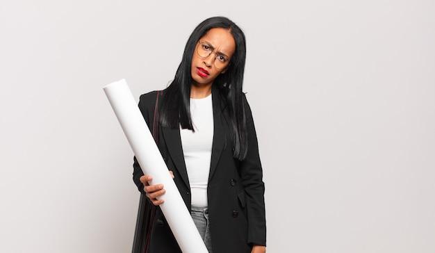 Jonge zwarte vrouw die zich verbaasd en verward voelt, met een stomme, verbijsterde uitdrukking op zoek naar iets onverwachts. architect concept