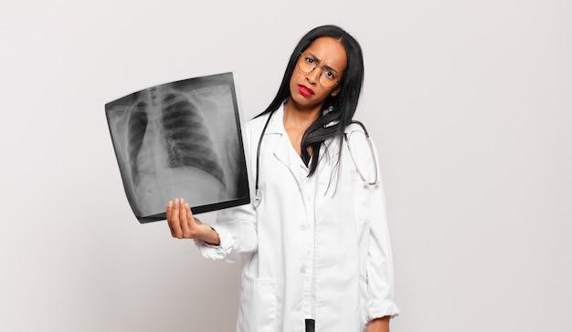 Jonge zwarte vrouw die zich verbaasd en verward voelt, met een stomme, verbijsterde uitdrukking op zoek naar iets onverwachts. arts concept