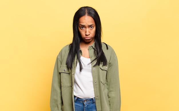 Jonge zwarte vrouw die zich verdrietig en gestrest voelt, overstuur vanwege een onaangename verrassing, met een negatieve, angstige blik