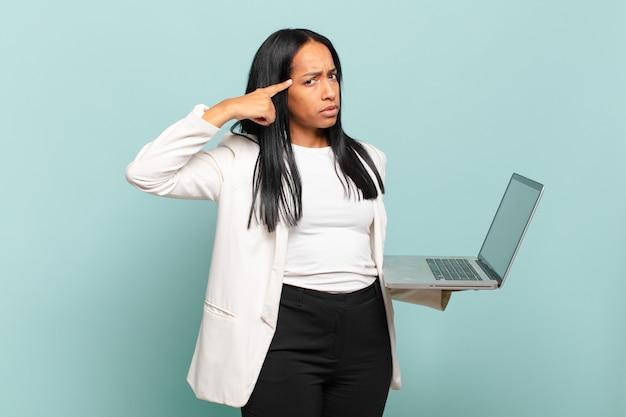 Jonge zwarte vrouw die zich verward en verbaasd voelt en laat zien dat je gek, gek of gek bent. laptopconcept