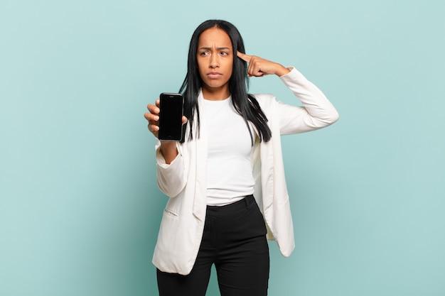 Jonge zwarte vrouw die zich verward en verbaasd voelt en laat zien dat je gek, gek of gek bent. slimme telefoon concept