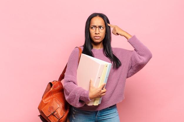 Jonge zwarte vrouw die zich verward en verbaasd voelt en laat zien dat je gek, gek of gek bent. studentenconcept